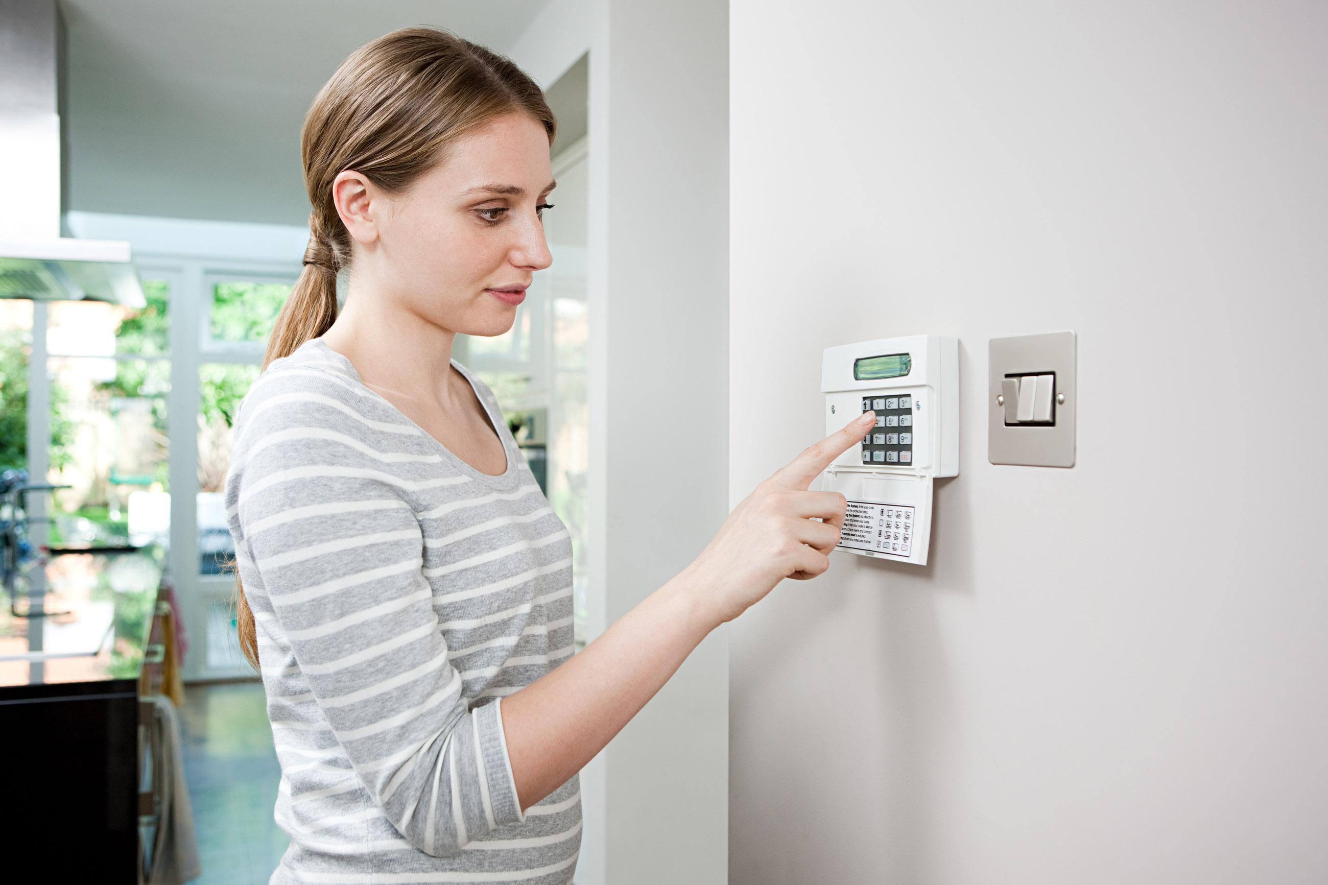 Woman setting burglar alarm --- Image by © Ocean/Corbis